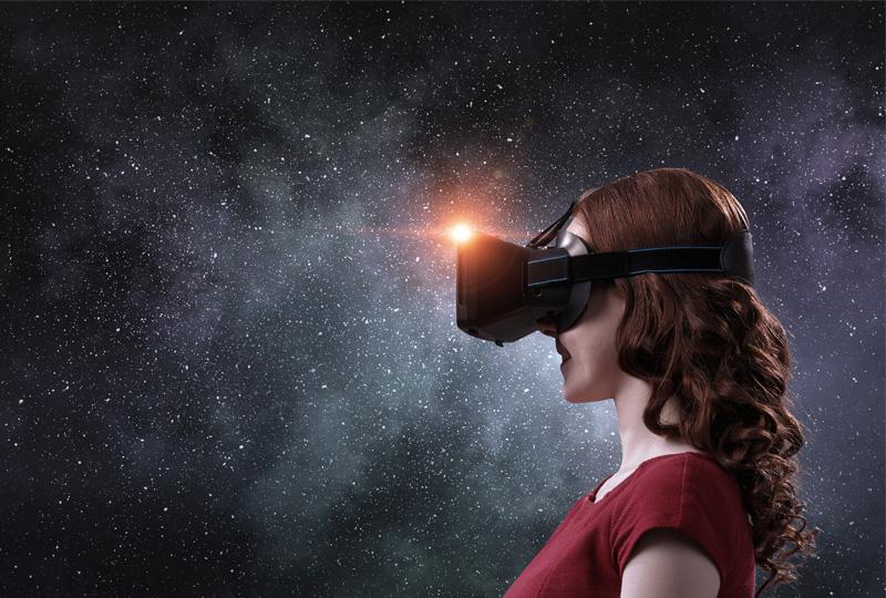 Nainen virtuaalilasit päässä, taustalla avaruus.